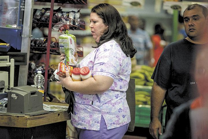 CAR15. CARACAS (VENEZUELA), 09/01/2015.- Una mujer carga en sus manos alimentos dentro de un supermercado privado hoy, viernes 9 de enero del 2015, en la ciudad de Caracas (Venezuela). El aÒo 2015 ha empezado en Venezuela con grandes colas en los supermercados en los que se sabe que ha llegado alg˙n producto de los que no hay suministro suficiente, como el detergente o los paÒales, ya que, tras dos aÒos de escasez, este mes de enero el problema ha alcanzado niveles crÌticos. EFE/MIGUEL GUTI…RREZ