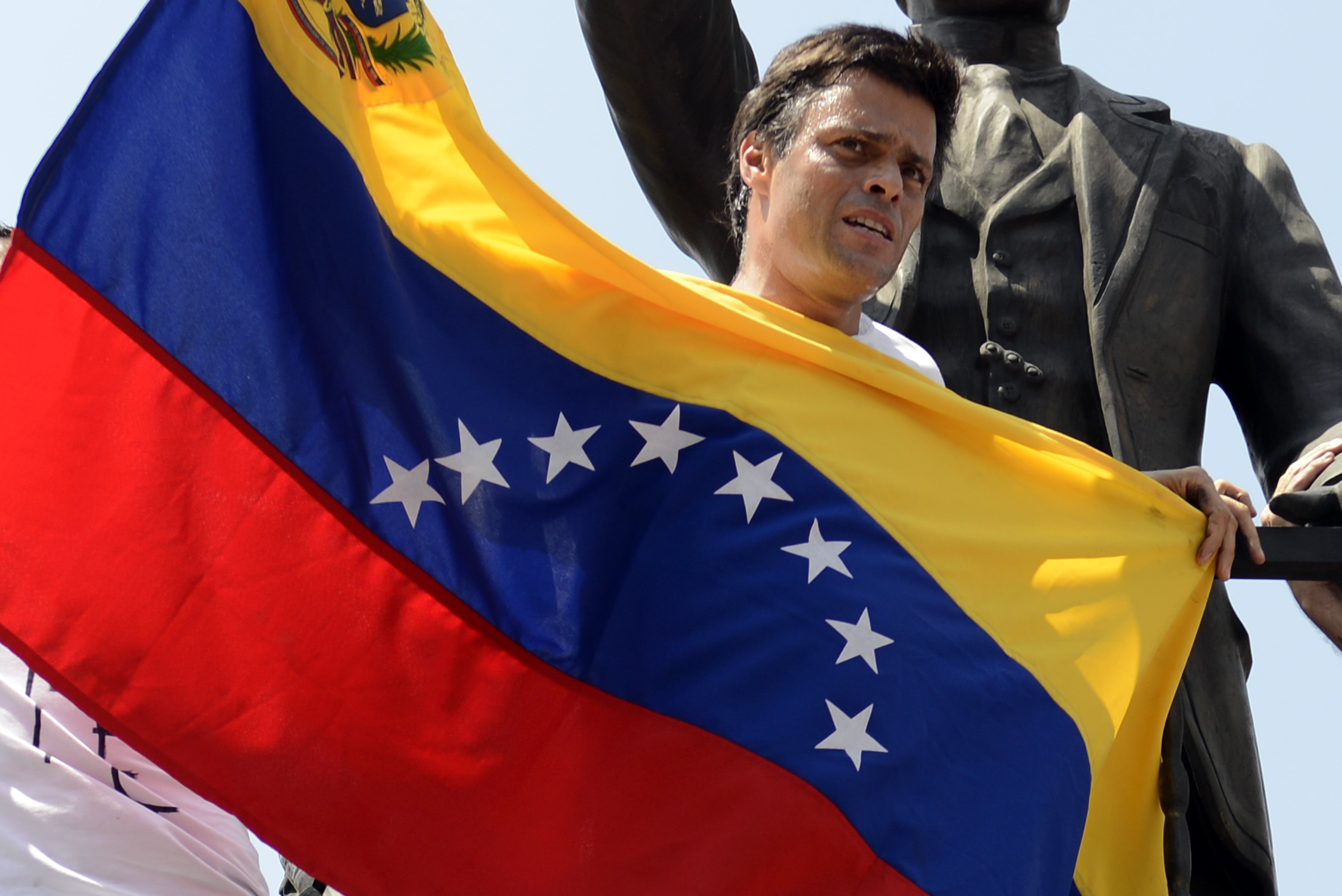 Leopoldo Lopez, an ardent opponent of Venezuela's socialist government facing an arrest warrant after President Nicolas Maduro ordered his arrest on charges of homicide and inciting violence, stands at the monument of Cuba's most important independence-era hero, Jose Marti, as he demonstrates with a national flag in Caracas before turning himself in to authorities, on February 18, 2014. Fugitive Venezuelan opposition leader Lopez, blamed by Maduro for violent clashes that left three people dead last week, appeared at an anti-government rally in eastern Caracas and quickly surrendered to the National Guard after delivering a brief speech. AFP PHOTO / LEO RAMIREZ